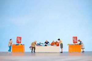 pessoas em miniatura comprando itens com desconto em uma mesa