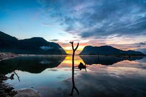 vista do nascer do sol com reflexo das montanhas no reservatório de klong hua chang