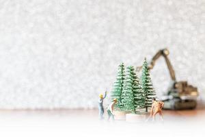 grupo de trabalhadores em miniatura preparando uma árvore de natal, conceito de decoração de natal foto