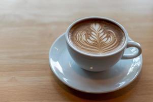 xícara de café latte art na mesa de madeira