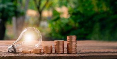 conceito de lâmpada e moedas empilhadas