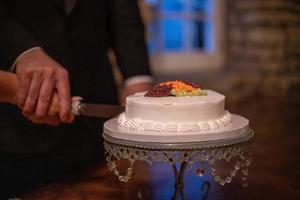 noiva e noivo cortam um pequeno bolo de casamento moderno na recepção