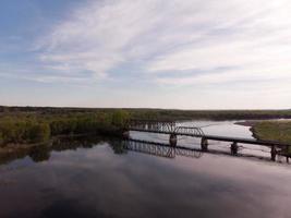 ponte ferroviária de madeira e aço sobre um rio sinuoso