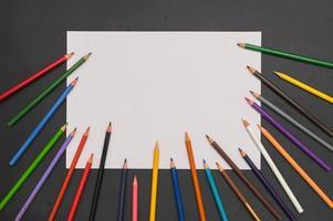 lápis multi coloridos e papel branco em fundo preto foto