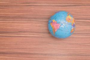 globo do mundo pequeno em fundo de madeira foto