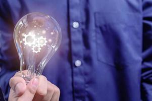 a mão de um homem de negócios segura uma lâmpada e um ícone de engrenagem