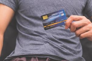 um homem segurando um cartão de crédito na mão foto