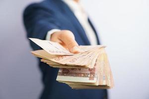 homem de negócios segurando dinheiro tailandês