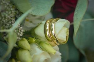 anéis de casamento em um buquê de flores brancas