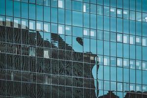 reflexos na fachada envidraçada de um prédio de escritórios