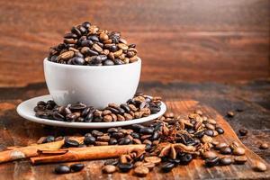grãos de café em uma xícara branca com pires e paus de canela em uma tábua de corte de madeira em uma mesa de madeira escura