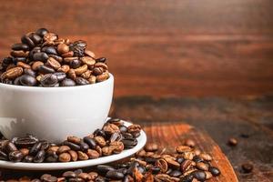grãos de café em uma xícara branca com pires em uma tábua de madeira sobre uma mesa de madeira escura