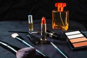 frasco de perfume e produtos cosméticos em um pano preto