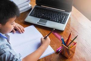menino fazendo lição de casa com notebook, laptop, grampeador e um copo de lápis em uma mesa de madeira foto