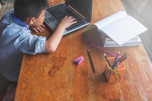 menino trabalhando em um laptop ao lado de um copo de lápis sobre uma mesa de madeira foto