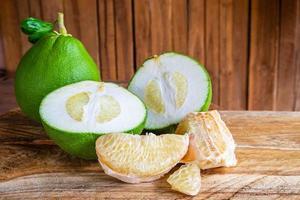 inteiros, fatiados e pedaços de pomelo em uma mesa de madeira