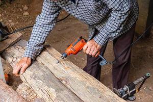homem usando furadeira em uma prancha de madeira em uma marcenaria foto