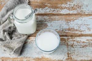 leite em copos em uma mesa de madeira foto