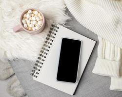smartphone em branco com chocolate quente foto