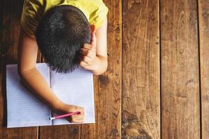 menino deitado no chão de madeira escrevendo no caderno foto