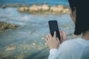 mulher usando um telefone perto da água
