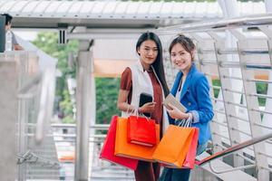 duas mulheres segurando sacolas de compras