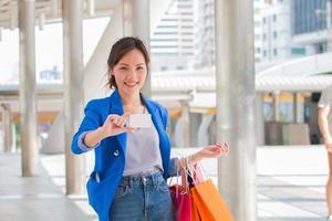 mulher segurando um cartão de visita em branco e sacolas de compras