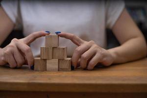 mulher empilhando blocos de madeira