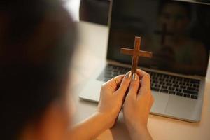 mulher orando perto de um laptop foto
