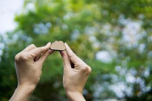 mãos segurando uma nuvem de madeira