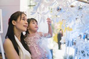 mãe e filha olhando para uma árvore de natal