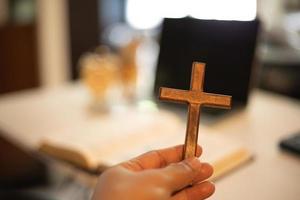 mão segurando uma cruz foto