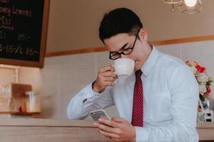 empresário tomando café e olhando para o telefone foto