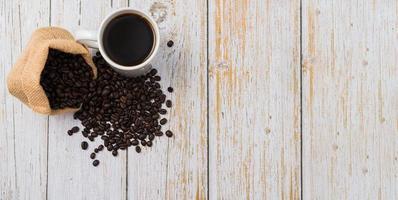 caneca de café e grãos de café na mesa