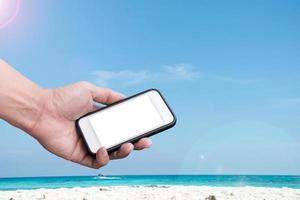 mão segurando um smartphone em uma praia e um fundo de céu azul