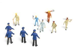 polícia em miniatura e uma multidão furiosa em um fundo branco