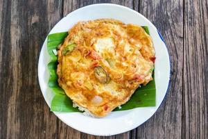 omelete com cebola, tomate e berinjela em uma textura rústica de madeira foto