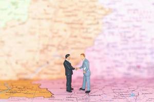 turistas em miniatura dando um aperto de mão em um conceito de plano de fundo, viagem e viagem de mapa mundial