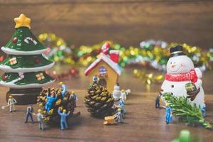pessoas em miniatura criando decorações de Natal em um fundo de madeira foto