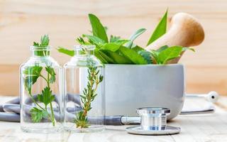 ervas frescas para óleos essenciais em garrafas e um pilão