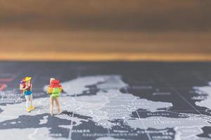 mochileiros em miniatura caminhando em um mapa-múndi, conceito de turismo e viagens foto