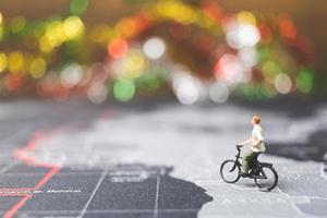 viajante em miniatura andando de bicicleta em um mapa-múndi, viajando e explorando o conceito do mundo foto