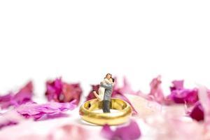 casal em miniatura se abraçando com uma aliança de casamento e pétalas de rosa isoladas em um fundo branco