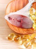 peixe e pílulas de óleo de peixe na madeira