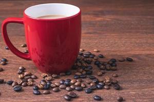 café em uma xícara de café vermelha ao lado de grãos de café derramados sobre uma mesa de madeira
