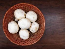 cogumelos brancos em uma cesta de vime sobre um fundo de mesa de madeira foto