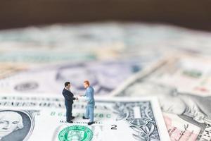 Empresários em miniatura com fundo de notas de dólar americano