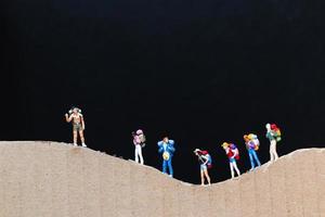 viajantes em miniatura com mochilas caminhando em uma montanha de papel, conceito de viagem e trekking foto
