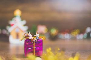 pessoas em miniatura em uma caixa de presente com decoração de celebração de Natal ao fundo