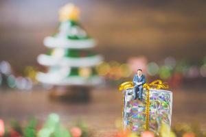 pessoas em miniatura em uma caixa de presente com fundo de celebração do dia de natal